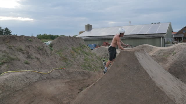 a young man shoveling to fix repair his his bmx bike bicycle dirt track with jumps. - bicycle trail outdoor sports stock videos & royalty-free footage