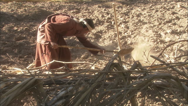 a young man shovels dirt behind a fence of sticks. - rievocazione video stock e b–roll