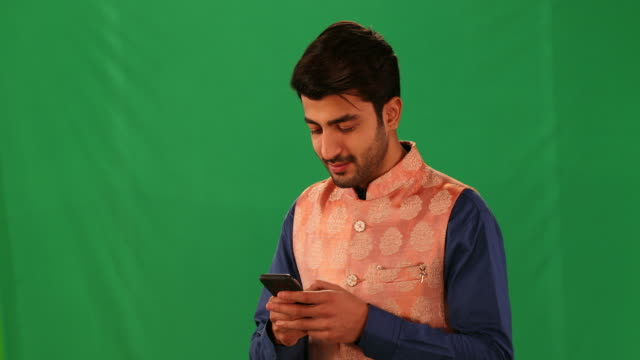 cu young man showing smartphone with a blank screen against a green background - blank screen stock videos & royalty-free footage