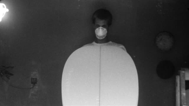 Young man showing surfboard to camera after having finished shaping the board