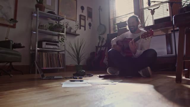 WS. Young man sings as he plays guitar in modern apartment.