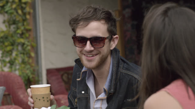 Young man sips coffee and laughs with friends at outdoor caf_