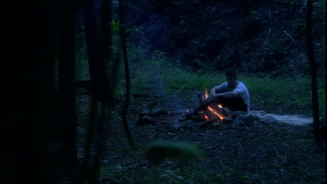 a young man sits by an open campfire. - reenactment stock videos & royalty-free footage
