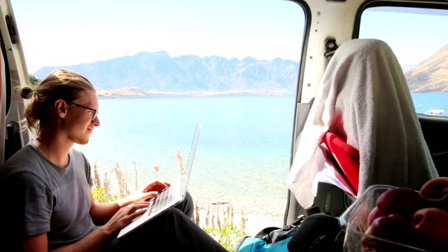 vidéos et rushes de young man sits in camper van enjoying the mountain lake view - lunettes de vue