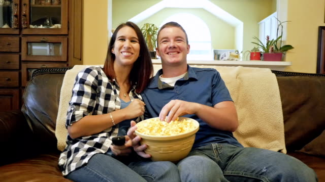 Young man sits next to girlfriend to watch television and eat popcorn