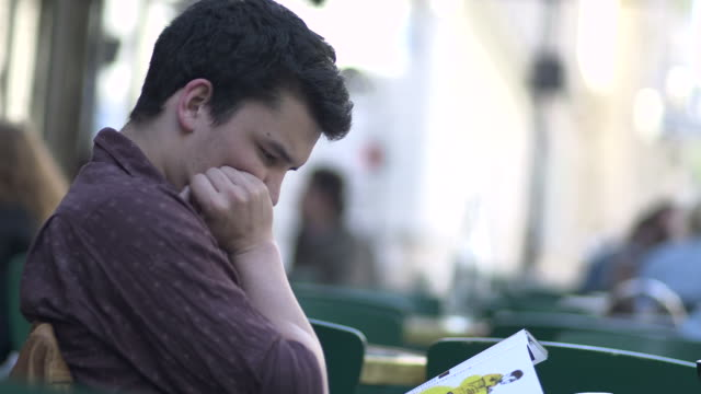 vidéos et rushes de young man sits outside reading - magazine