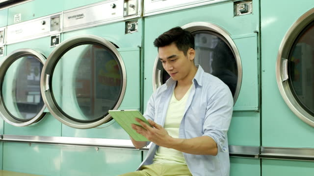 mls a young man sits waiting in a launderette - launderette stock videos & royalty-free footage