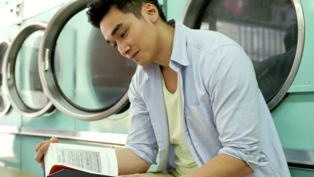 mls a young man sits waiting in a launderette - fully unbuttoned stock videos & royalty-free footage
