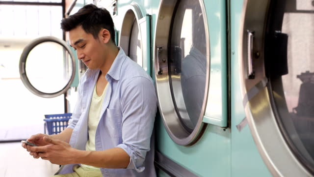 ms a young man sits with his smartphone in a launderette - laundromat stock videos & royalty-free footage