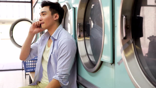 ms a young man sits with his smartphone in a launderette - fully unbuttoned stock videos & royalty-free footage