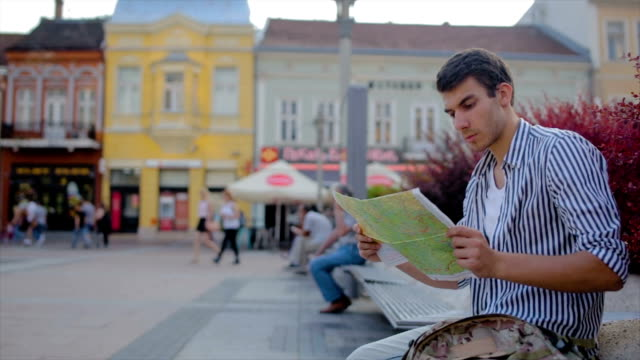 Young man sitting and looking on the map in the city,travel concept