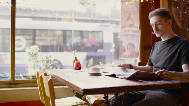 a young man sitting at a table in a coffee shop in manchester - ein mann allein stock-videos und b-roll-filmmaterial