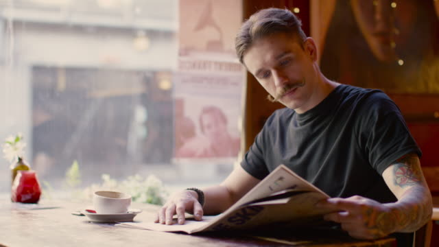 a young man sitting at a table in a coffee shop in manchester - zeitschrift stock-videos und b-roll-filmmaterial