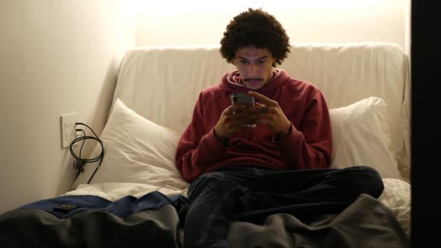vídeos de stock, filmes e b-roll de young man sitting in bed texting - pouca luz