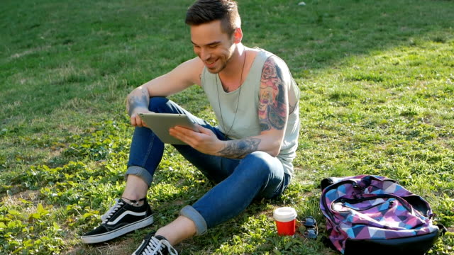 Young man sitting in park with digital tablet and using wi-fi internet