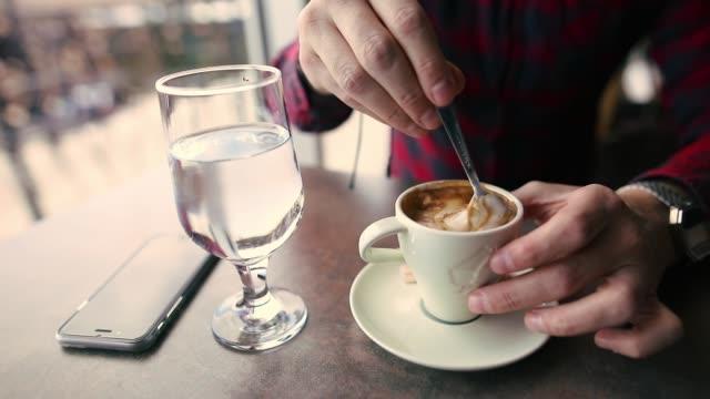 young man sitting in rooftop coffee shop near window, mixing espresso coffee - coffee break stock videos & royalty-free footage