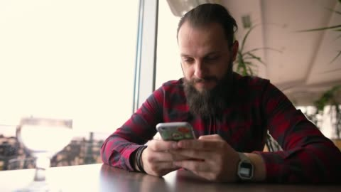 young man sitting in rooftop coffee shop near window, using phone, sending text messages - one young man only stock videos & royalty-free footage