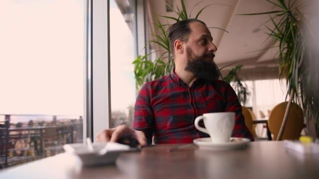 young man sitting in rooftop coffee shop near window - tartan stock videos & royalty-free footage