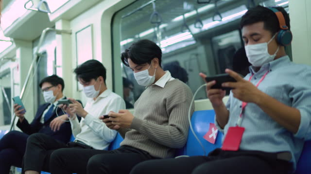 young man sitting in social distancing while travelling safely in metro train using mobile phones - rail transportation stock videos & royalty-free footage