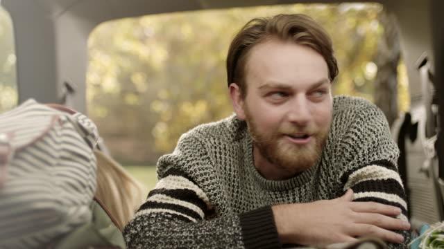 Junger Mann sitzt im Auto, gestikulieren mit den Händen und Blick in die Kamera