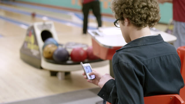 stockvideo's en b-roll-footage met ms young man sitting near bowling alley and hugging a woman - bowlingbaan