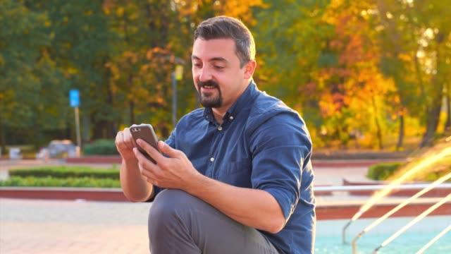 Young man sitting near fountain using smart phone
