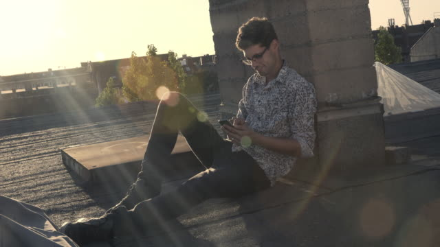 young man sitting next to a chimney uses his smartphone - brille stock-videos und b-roll-filmmaterial