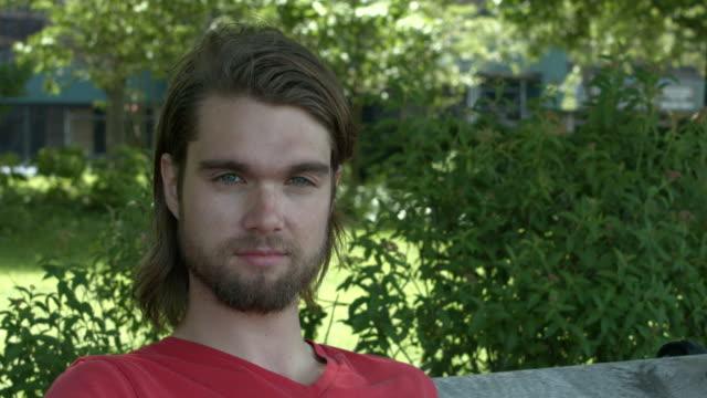 vídeos y material grabado en eventos de stock de a young man sitting on a bench looking at camera outside in new york city - sólo hombres jóvenes