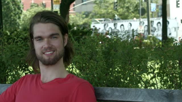 vídeos y material grabado en eventos de stock de a young man sitting on a bench outside looking at camera in new york city - sólo hombres jóvenes