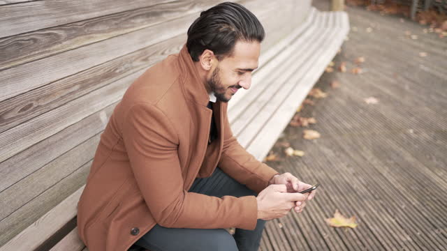 a young man sitting on a park bench checking his phone - indian ethnicity stock videos & royalty-free footage