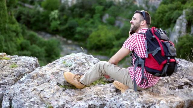 Jonge man zittend op een klif en praten over de telefoon