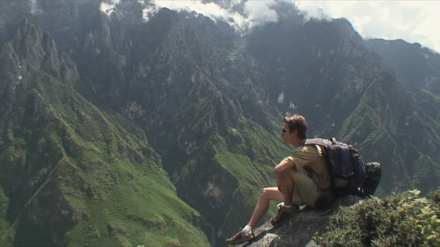 WS Young man sitting on cliff / Tiger Leaping Gorge, China