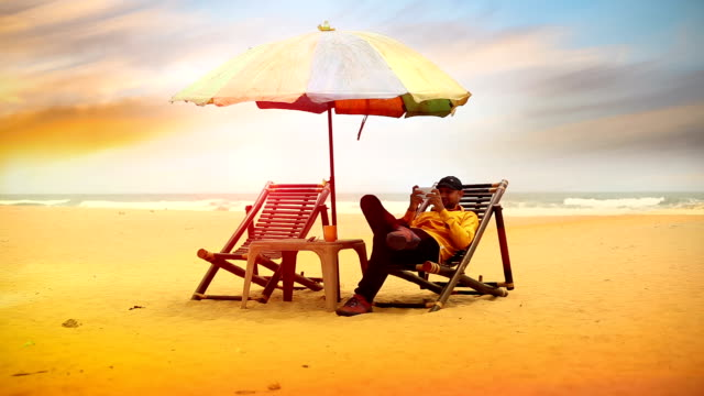 young man sitting on deck chair and using smartphone - beach umbrella stock videos and b-roll footage