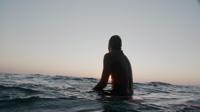 sm young man sitting on his surfboard waiting for a wave at sunset - using a paddle stock videos & royalty-free footage