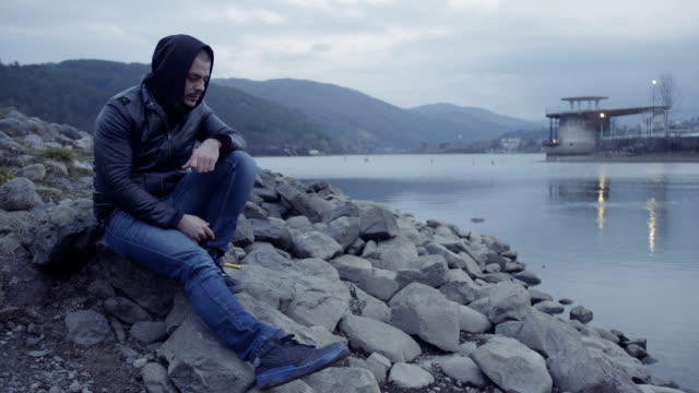 young man sitting on lake shore and contemplating - broken heart stock videos and b-roll footage