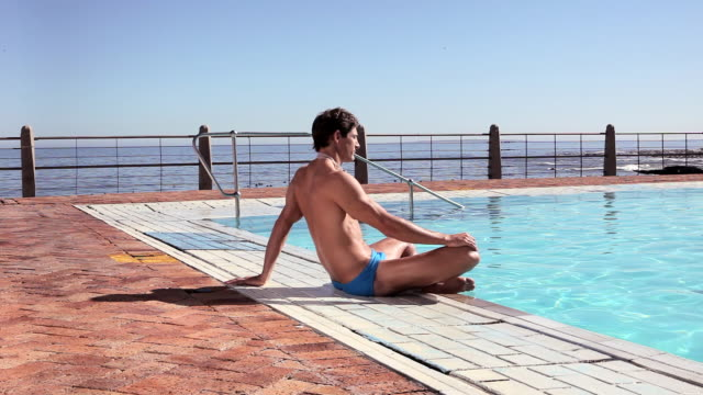 young man sitting on poolside - poolside stock videos & royalty-free footage
