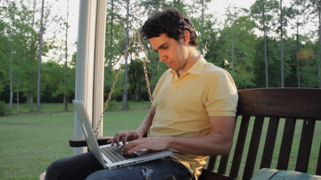 MS Young man sitting on porch working on laptop / Madison, Florida, USA