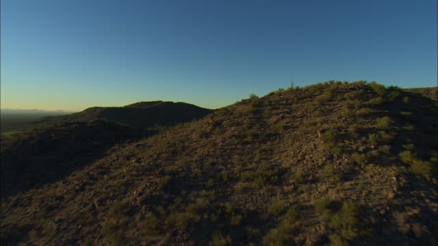 AERIAL ZI Young man sitting on rocky saguaro cactus covered hill, Tucson, Arizona, USA