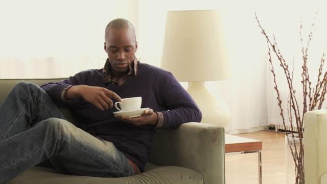 MS PAN Young man sitting on sofa drinking coffee / New York City, New York, USA