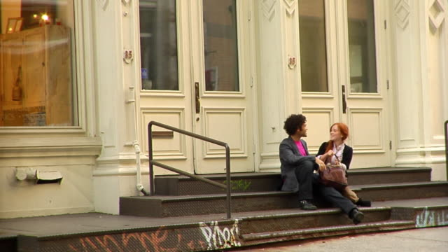 WS Young man sitting on steps in SoHo/ Girlfriend arriving to meet him/ They kiss and dance on the steps before leaving/ New York City