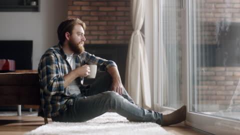 junger mann auf dem boden sitzen und kaffee trinken - kaffee stock-videos und b-roll-filmmaterial