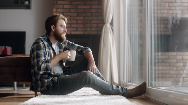 young man sitting on the floor and drinking coffee - barba peluria del viso video stock e b–roll