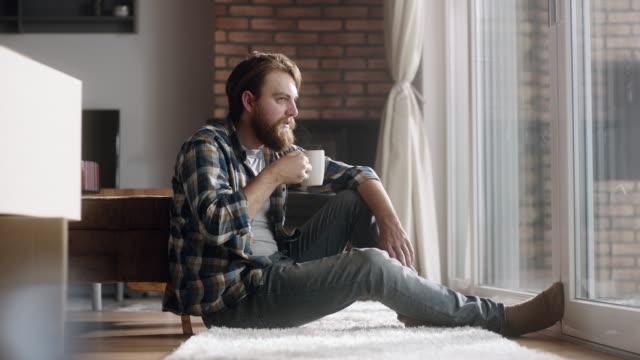 junger mann auf dem boden sitzen und kaffee trinken - vollbart stock-videos und b-roll-filmmaterial