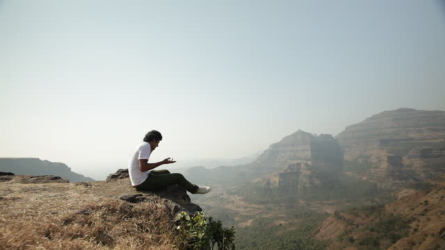 Young man sitting on the rock and talking on the mobile phone