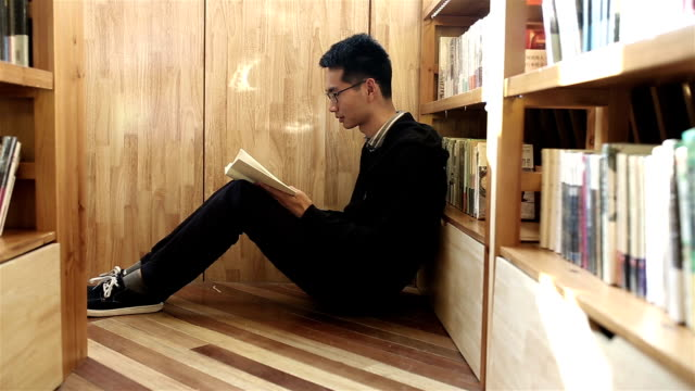 Young man sitting reading book on the ground