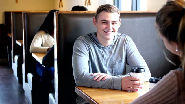 stockvideo's en b-roll-footage met jonge man zitten met tienermeisje in coffeeshop - 18 19 years