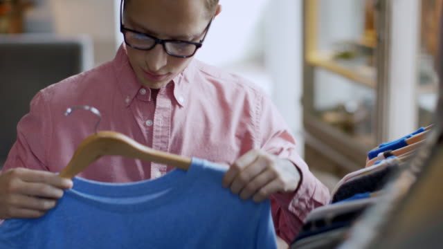 Young man sizes up t-shirt and returns it to rack in trendy clothing shop