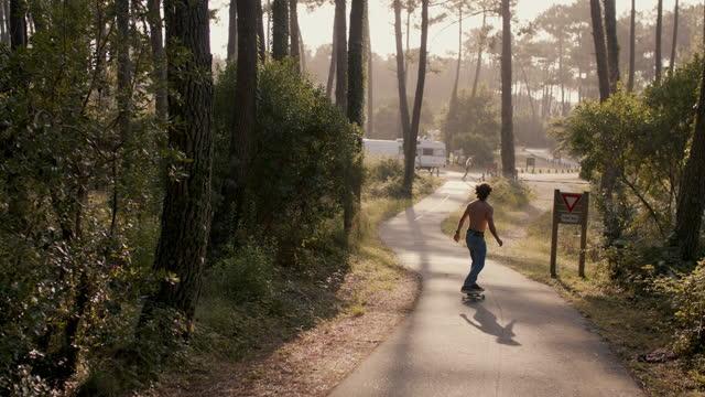 vídeos y material grabado en eventos de stock de young man skateboarding down hill in forest in sun - pasear en coche sin destino
