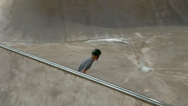 WS PAN Young man skateboarding in skatepark/Singapore