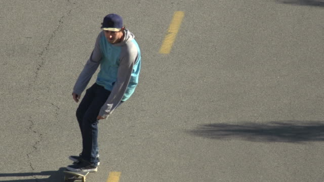 A young man skateboarding in the middle of the street. - Slow Motion